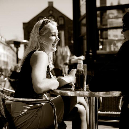 Smiling woman at a café at Sankt Hans Torv in Copenhagen, Denmark
