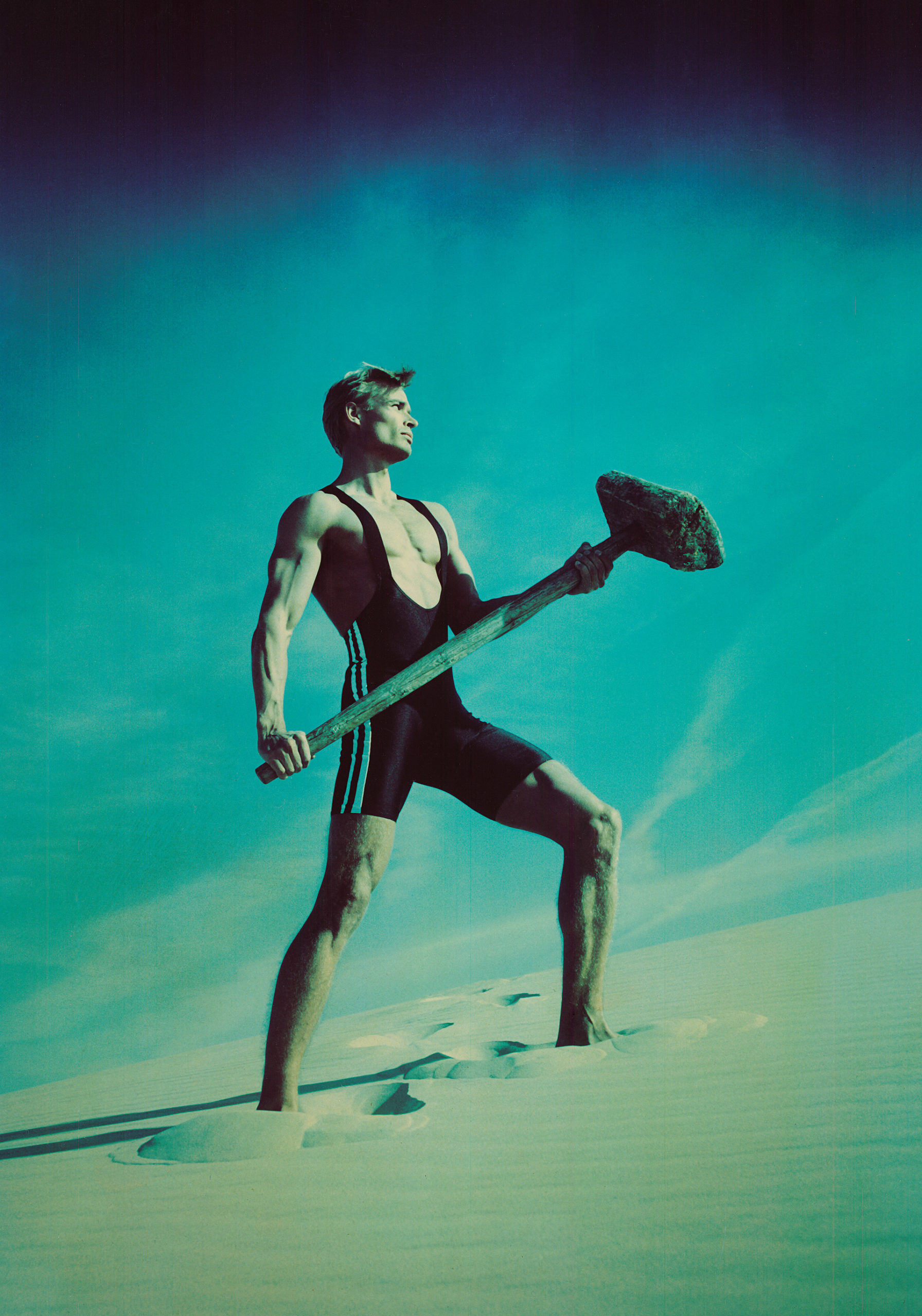 Man standing on a sand dune holding a hammer in Råbjerg Mile