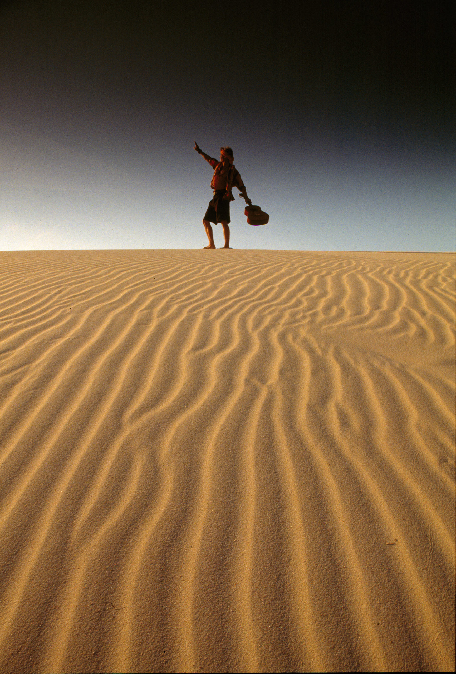 Man in a desert swinging a guitar