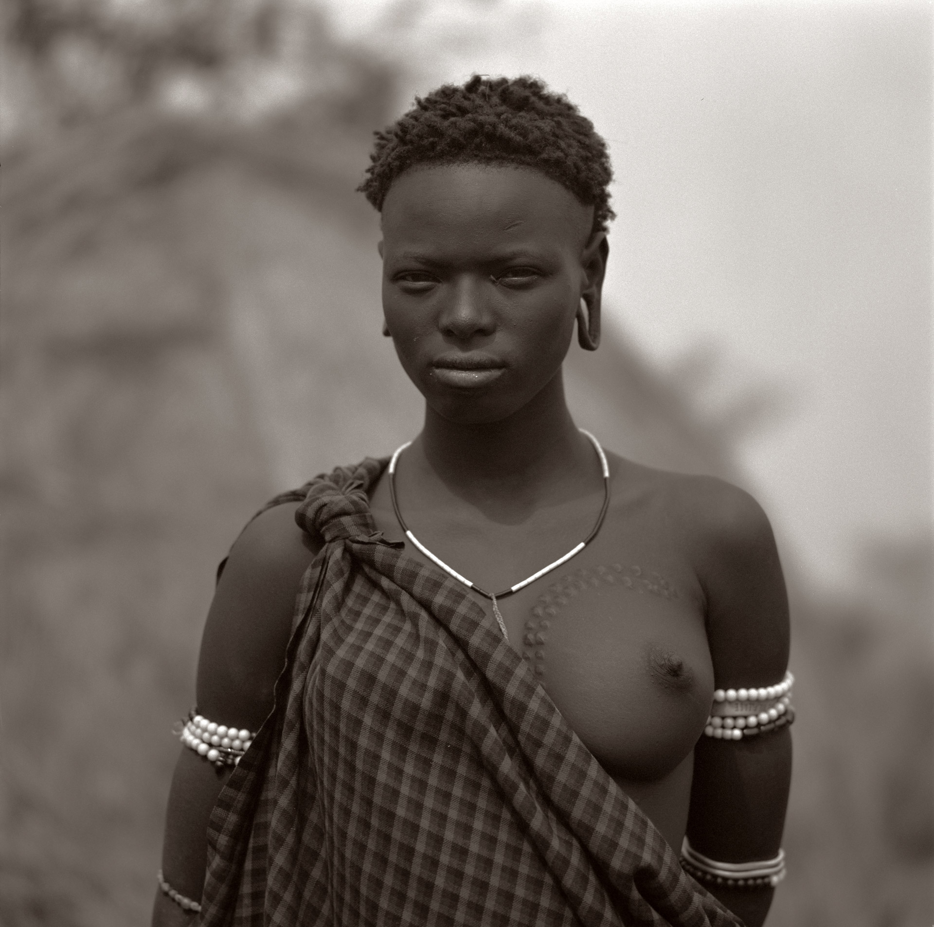 A woman from the Mursi tribe in front of her thatched house in Omo Valley