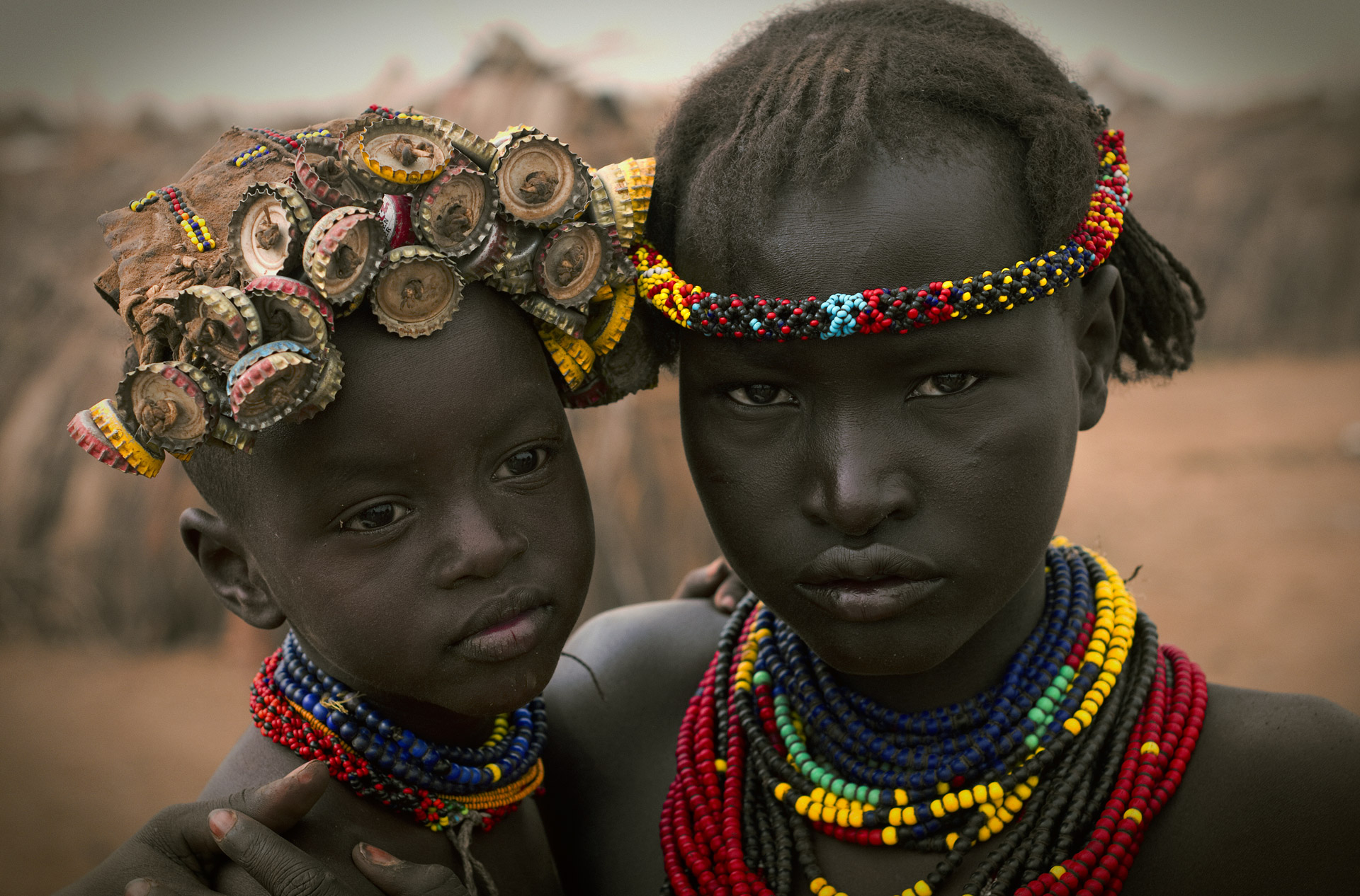 A young woman and her little sister with caps from bottles woven into her hair.