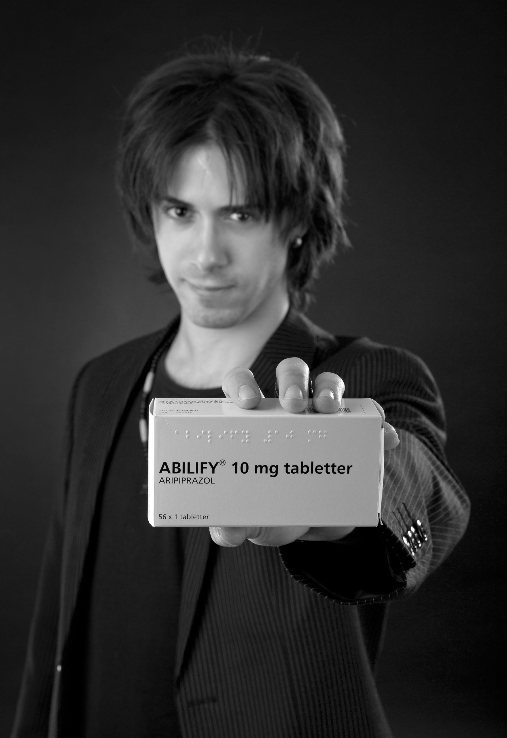 A young man showing abilify medicinal tablets