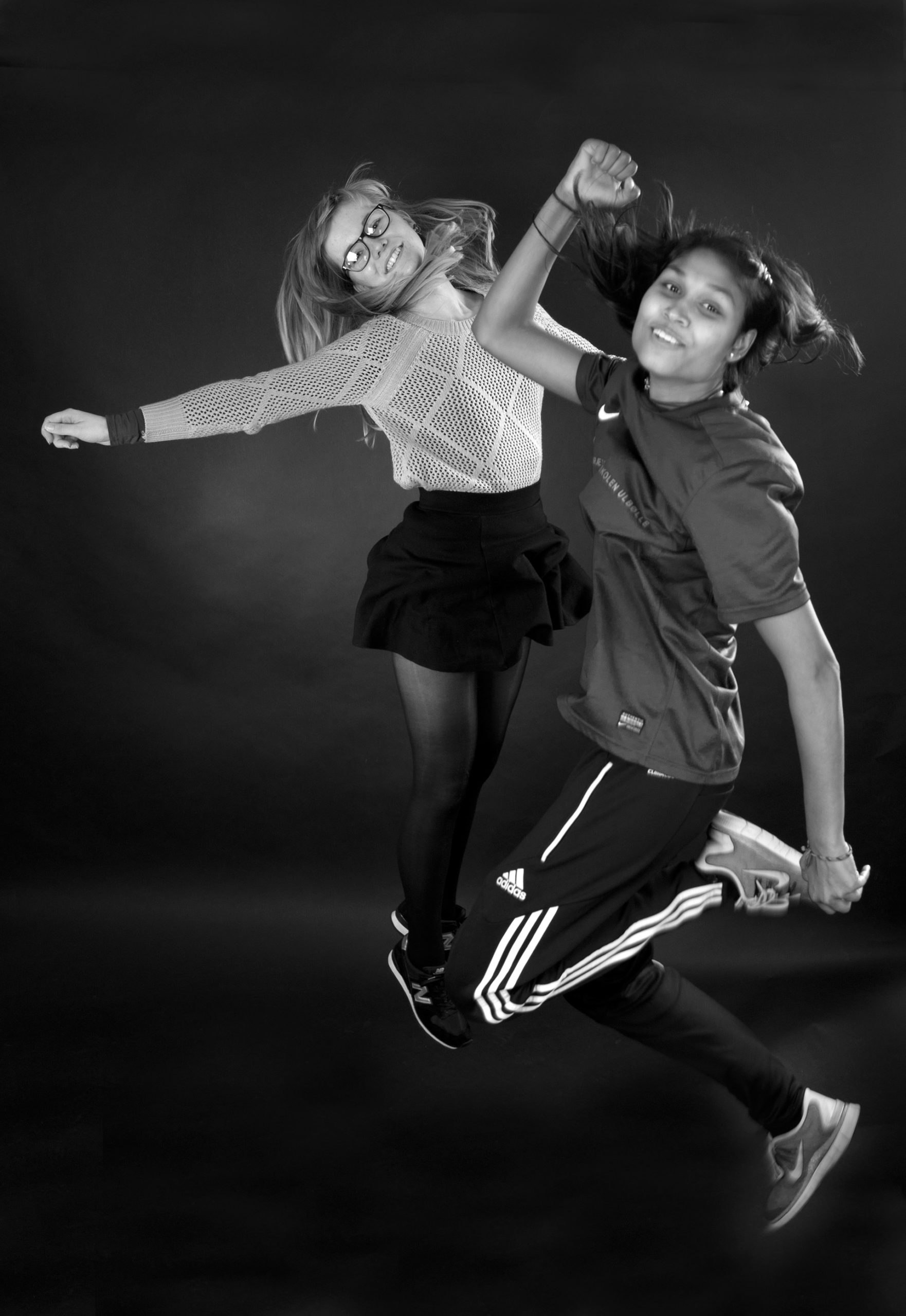 Two girls jumping for exhibition at Danish School of Education