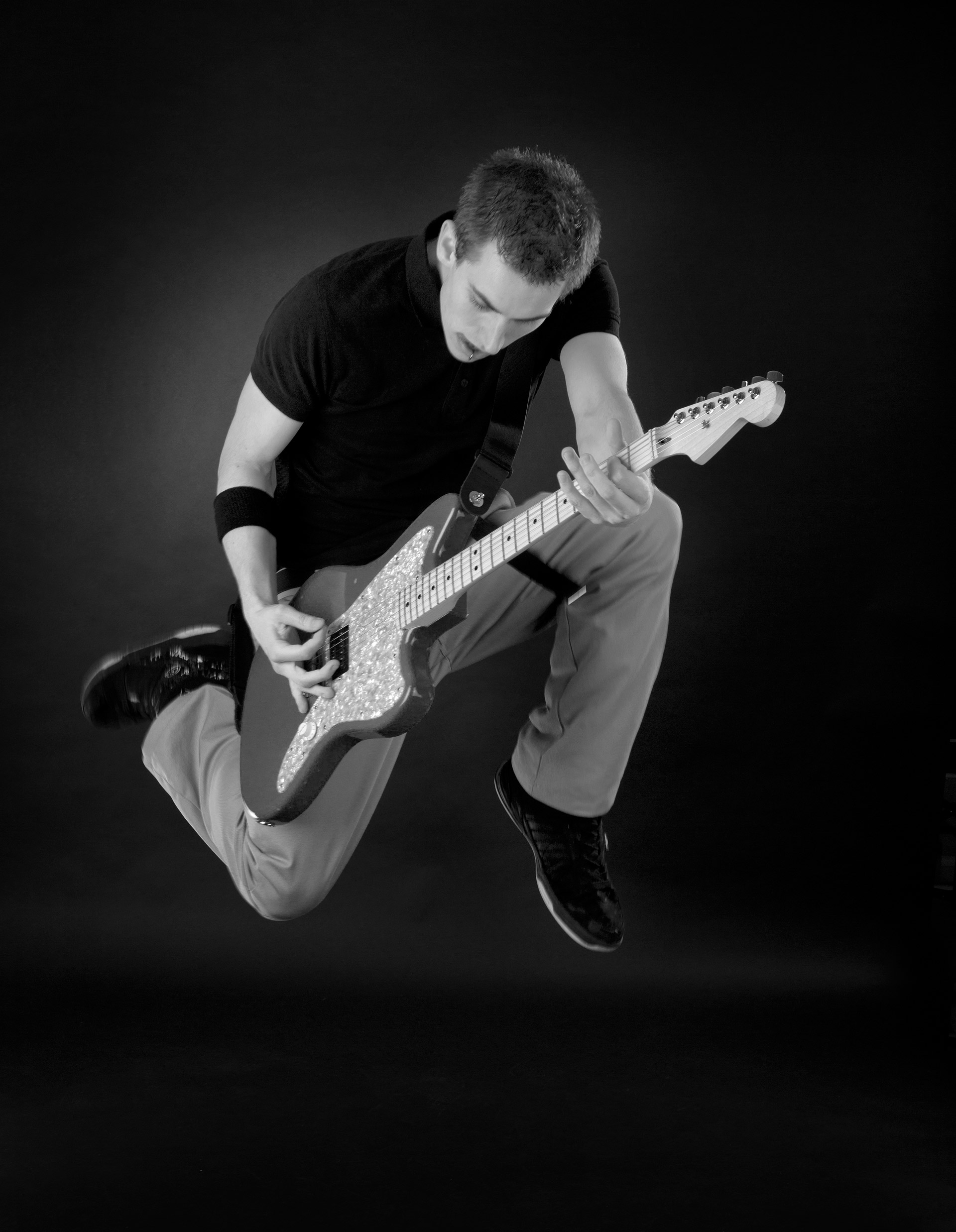 Man playing guitar while jumping for exhibition at Danish School of Education