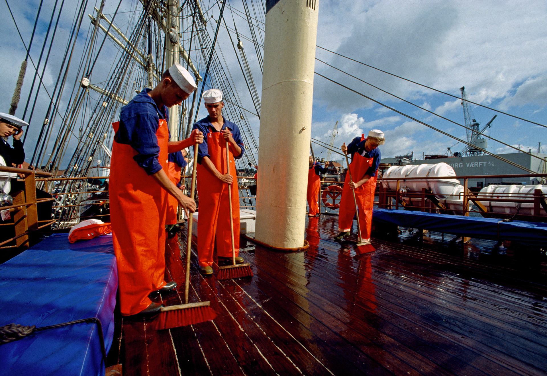 Men scrubbing the deck on Skoleskibet Danmark - the school ship Denmark