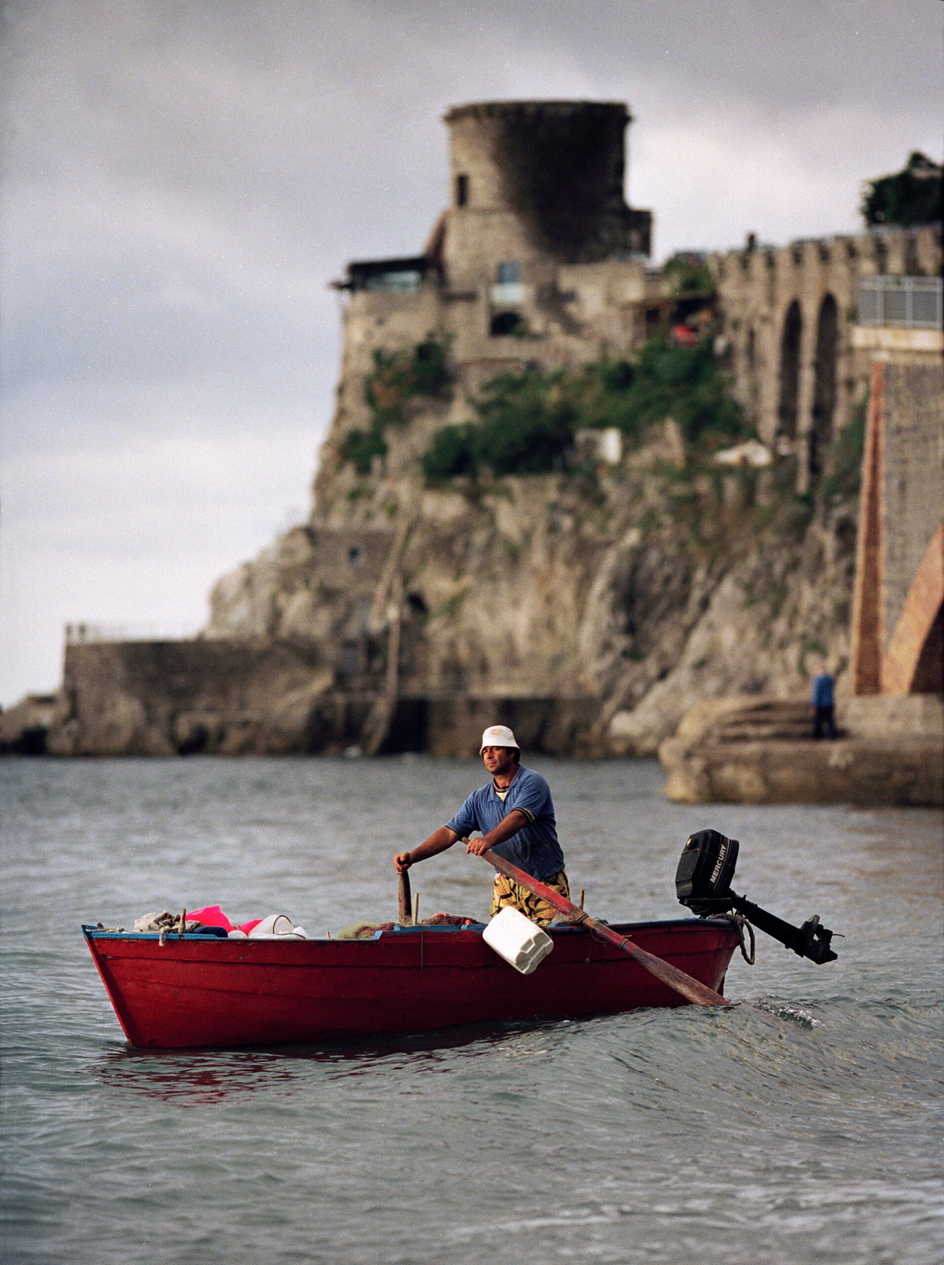 A fisherman in a small rowing boat off the Amalfi coast in Italy