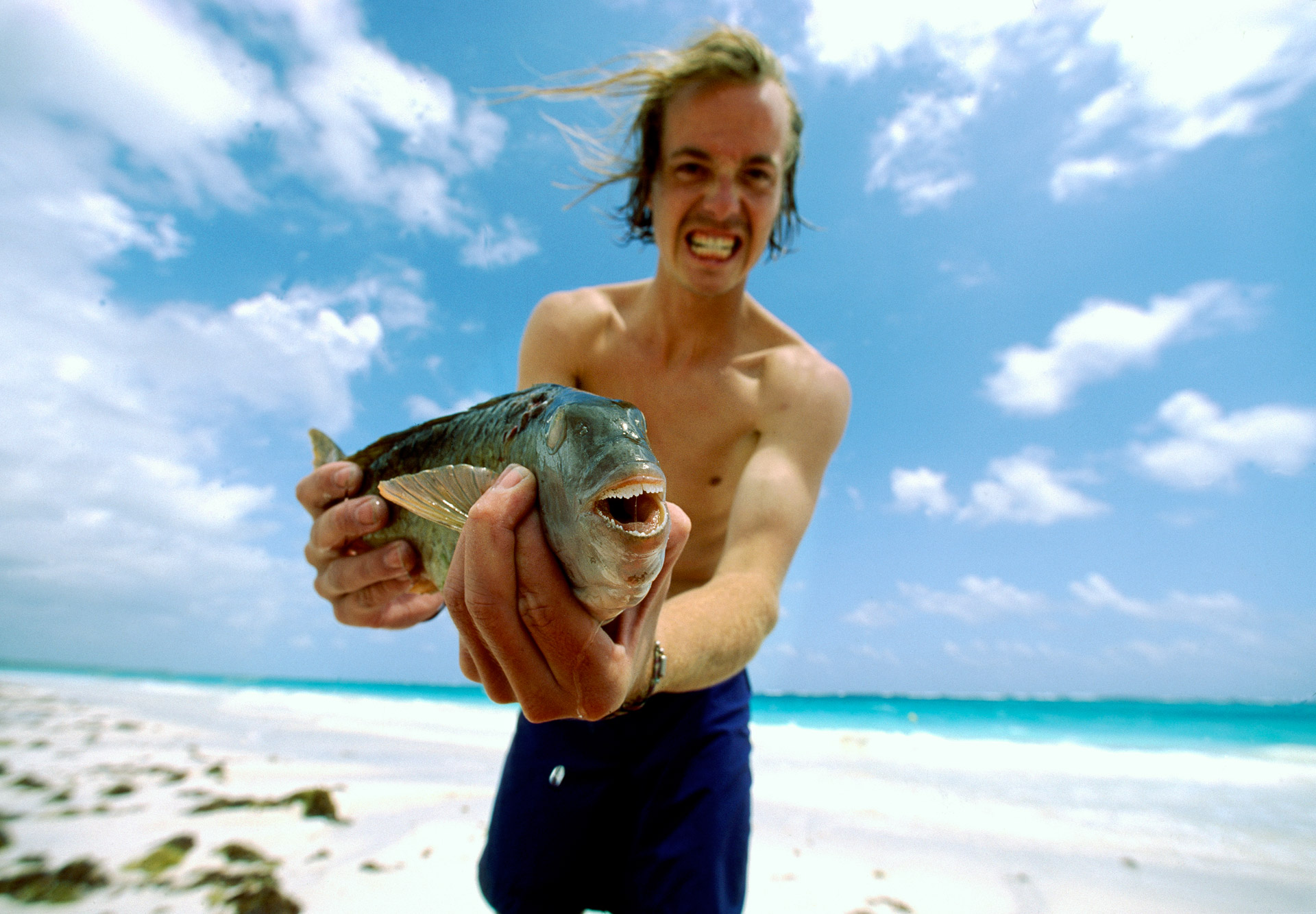 Man showing the teeth of a parrot fish in Tulum, Mexico