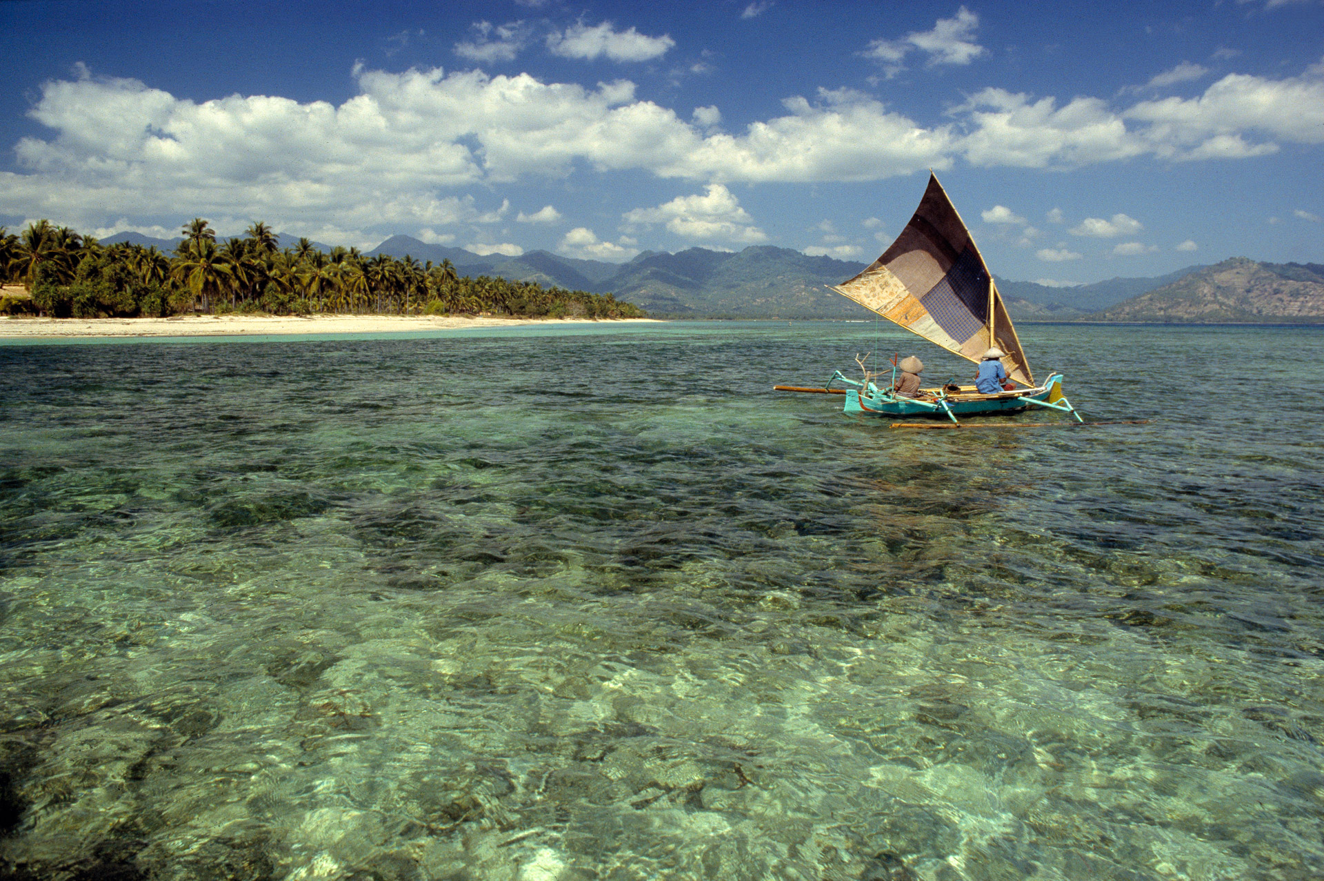 A dugout canoe sail across the clear sea off Gili Air while Lombok is seen in the horizon