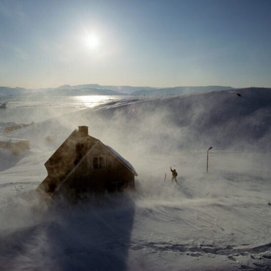 A man waves goodbye to the helicopter in Tiniteqilaaq near Ammassalik in Eastern Greenland