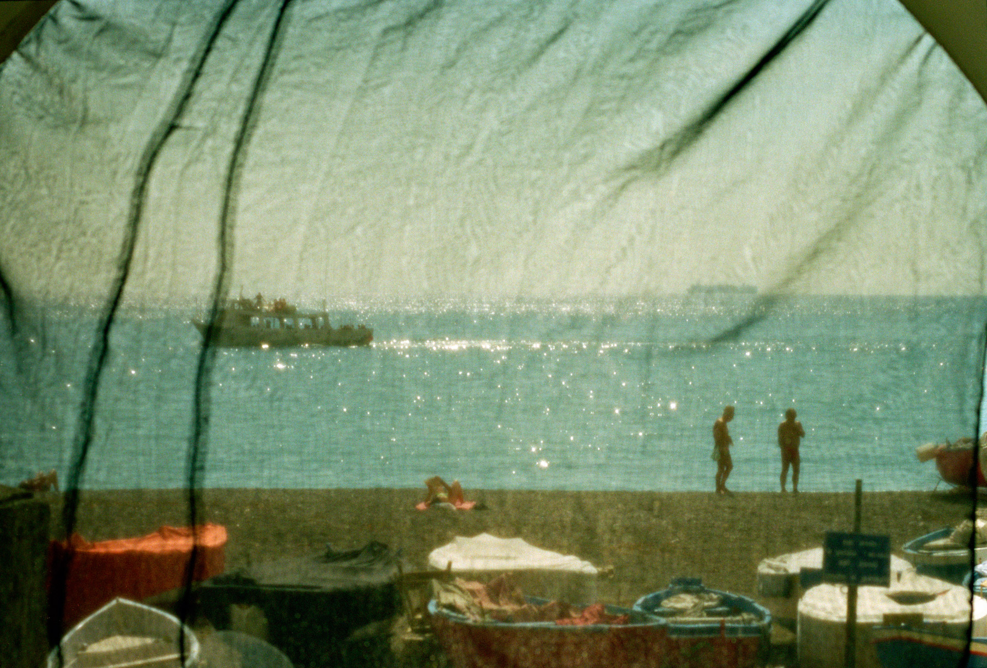 People at the beach seen through a fishing net at the Amalfi coast in Italy