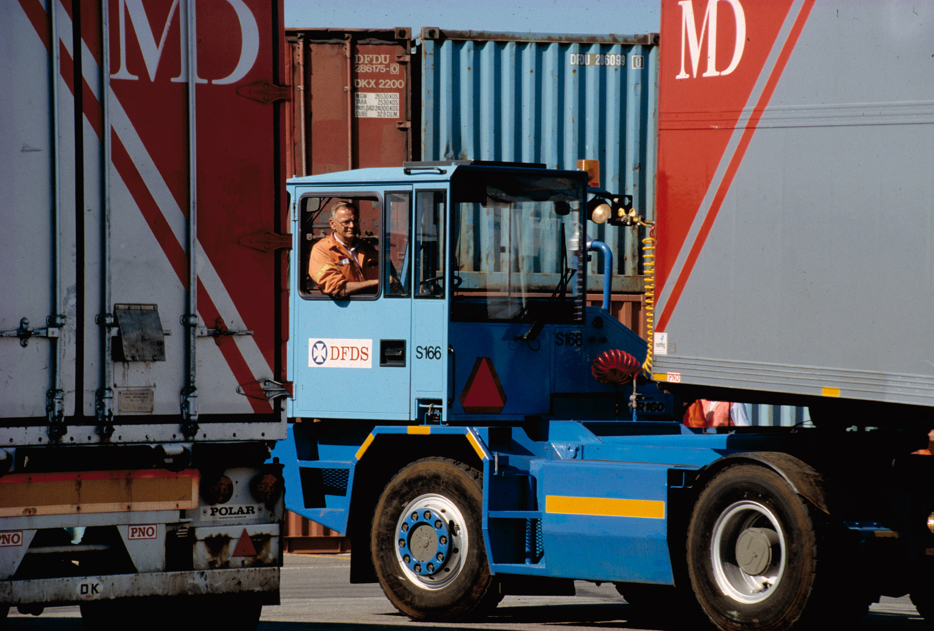 A man maneuvers MD-Foods containers in Esbjerg Harbour