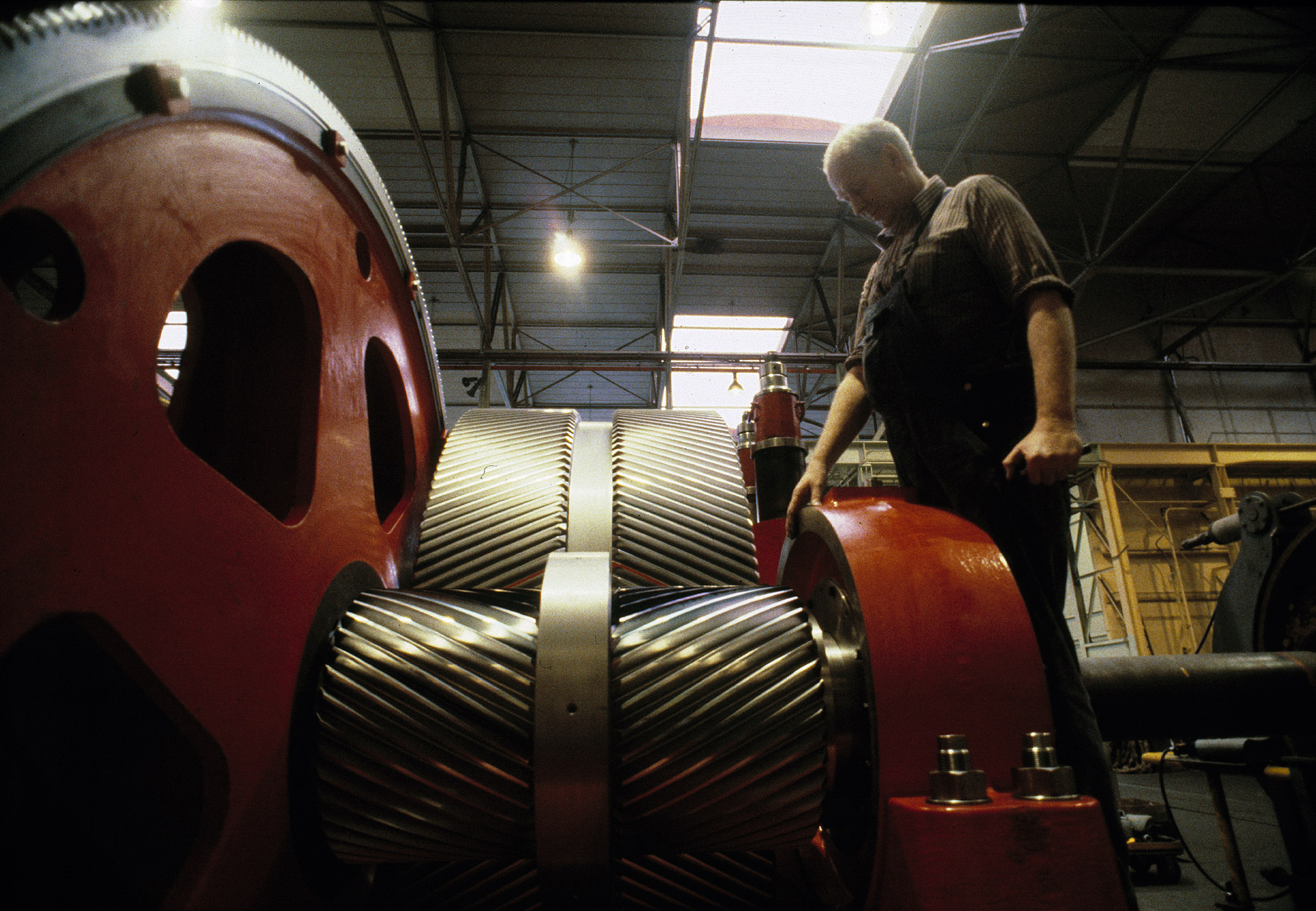 A man inspects a huge gear at FLS Industries in Valby