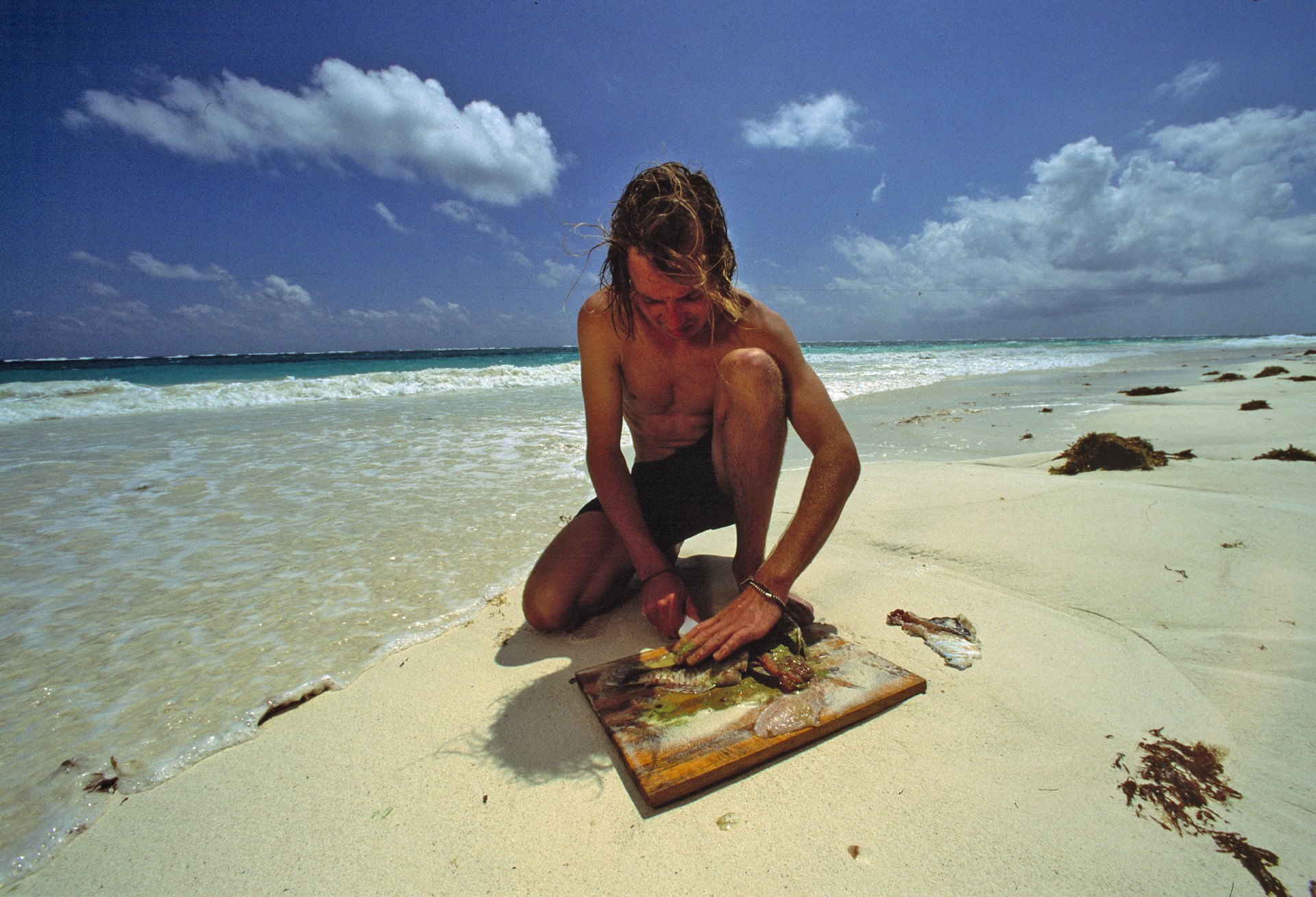 Joshua cleaning a parrot fish on the beach in Tulum
