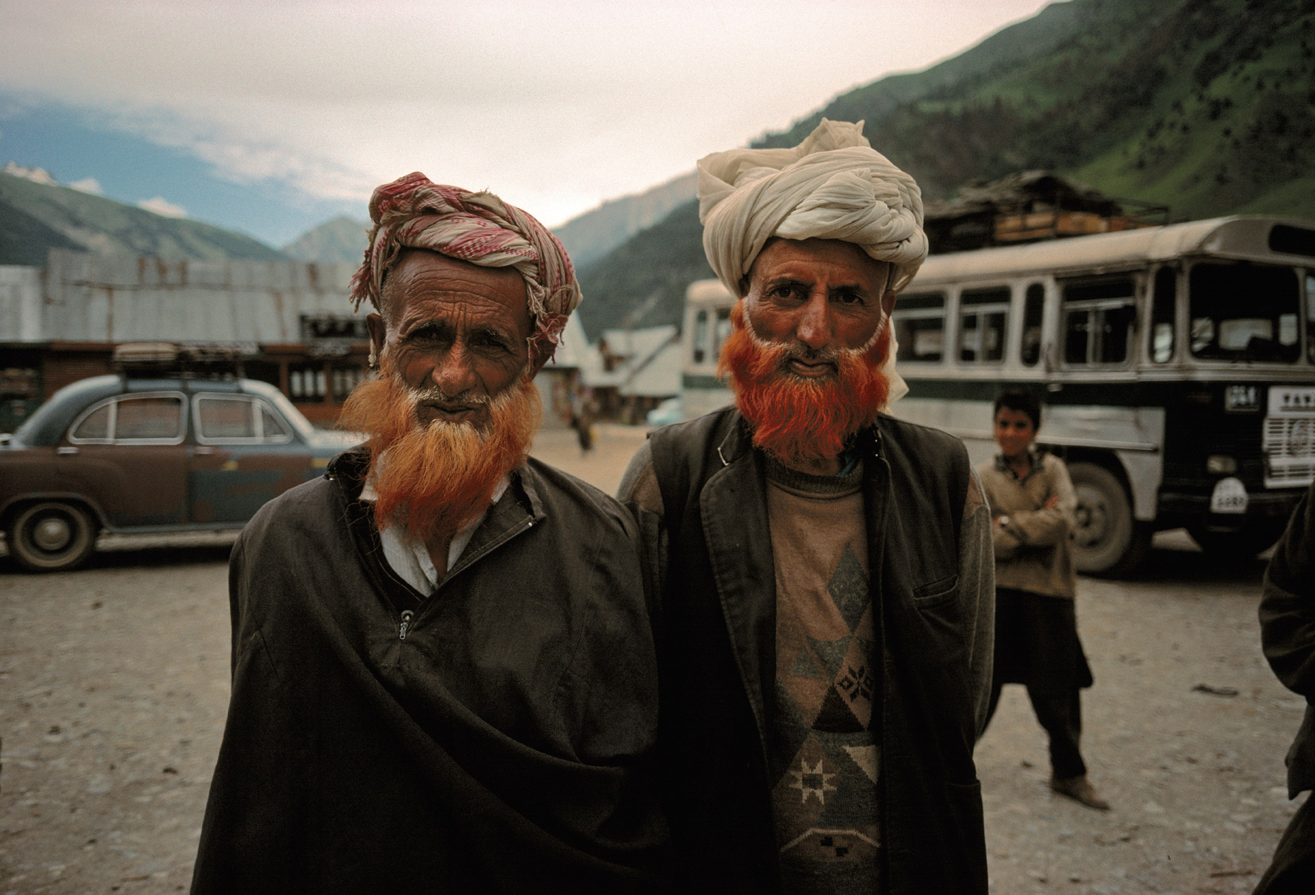 Two Muslim men with their beards dyed in orange color waiting at the bus station in Sona Marg in Kashmir