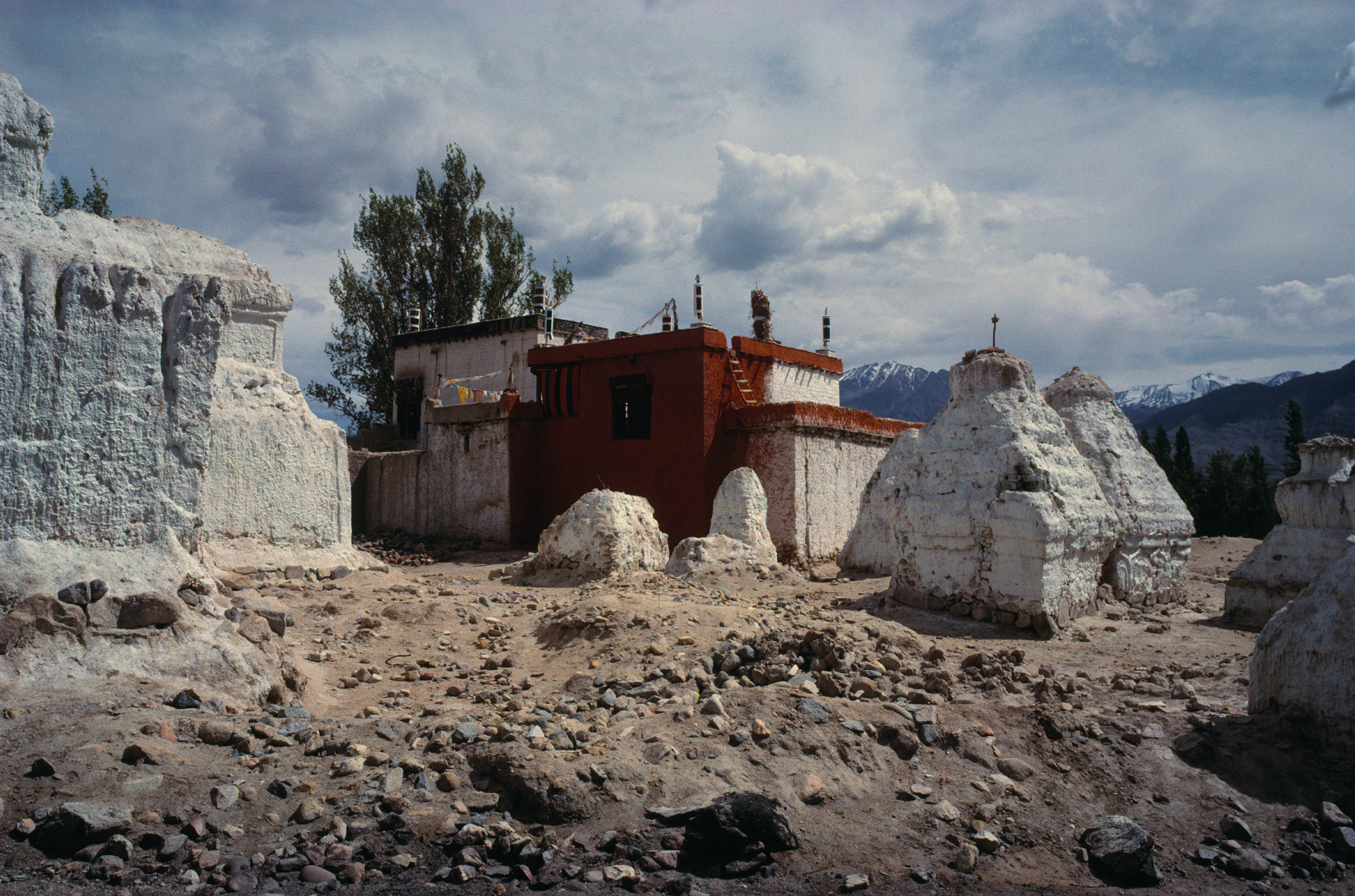Red painted house surrounded by Stupas beneath Thiksey Monastery in Ladakh, India
