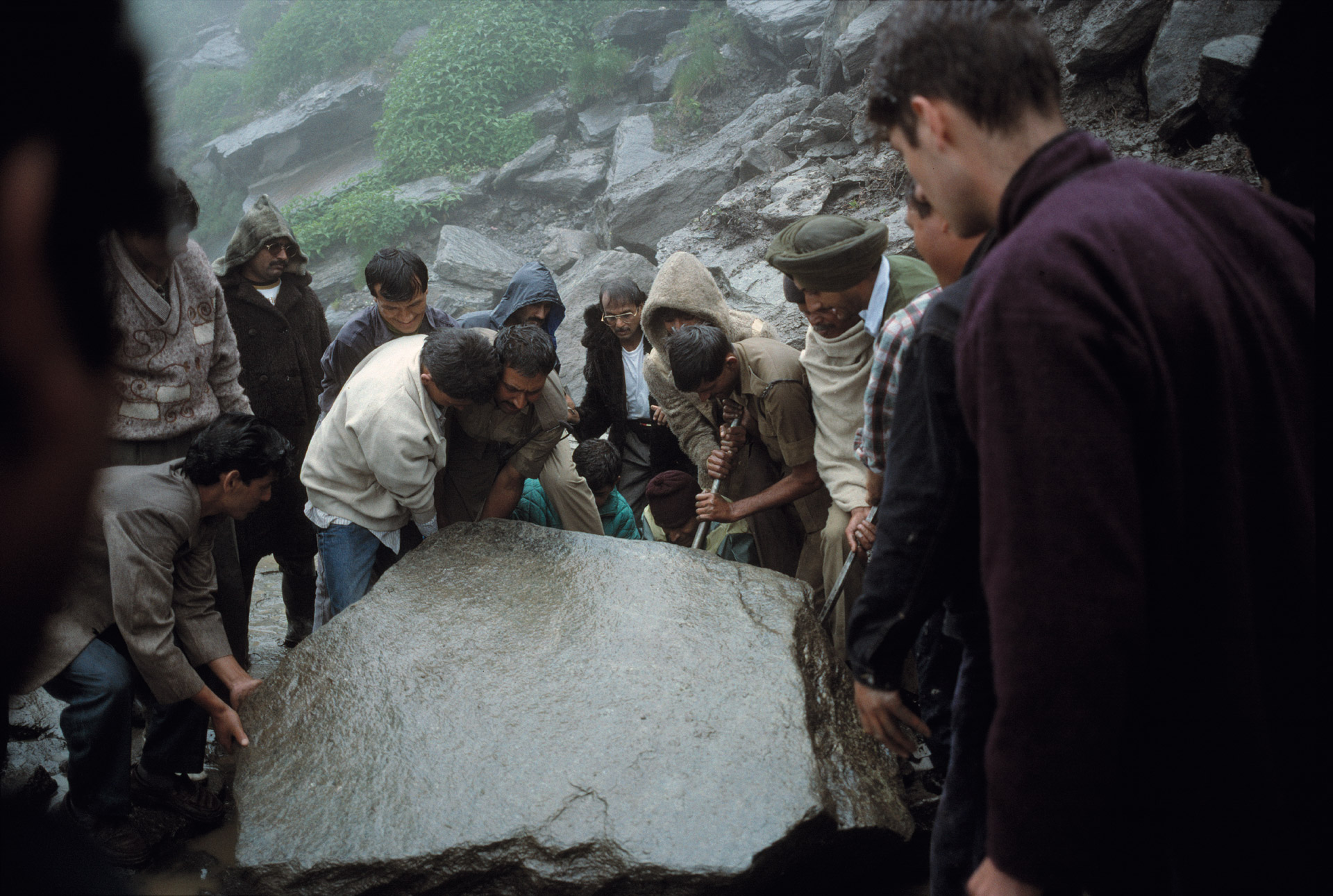Indian civilians, soldiers and a few tourists collaborate to remove a big stone that blocked the road in the Himalaya Mountains in India