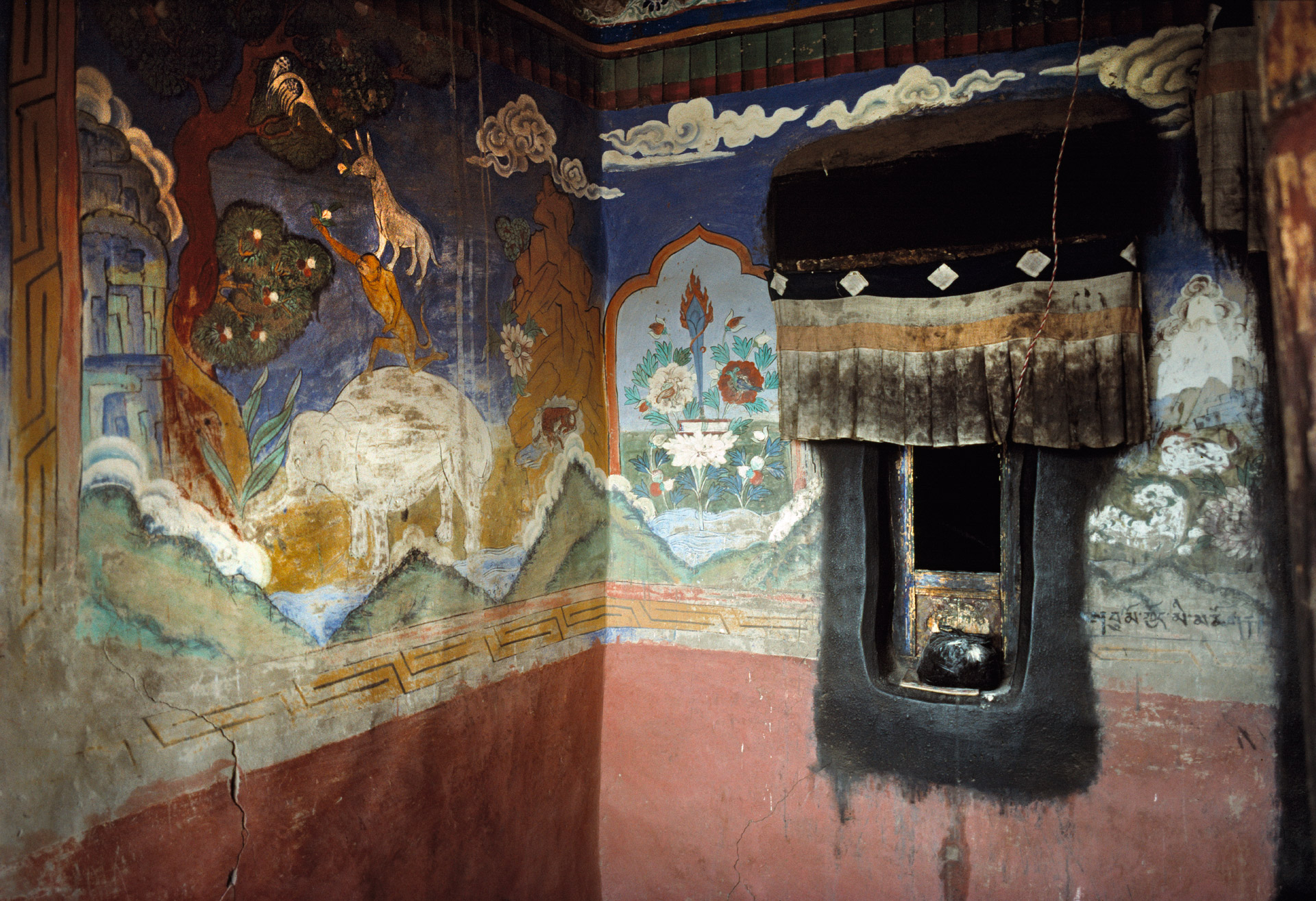 Religious murals depicting a donkey standing on the shoulders of a monkey which again is standing on the shoulders of an elephant at Thiksey Monastery in Ladakh